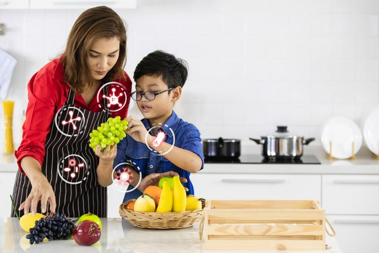 A mother and son in the kitchen choosing probiotic fruits
